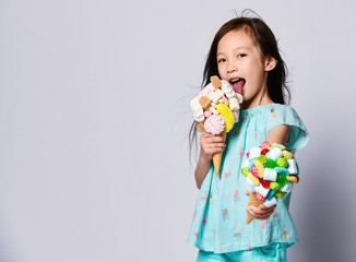 Happy asian baby girl kid eats licks a big ice-cream in waffles cones with tasty toppings and offers another one us
