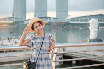 Fototapete - Young Woman traveling with hat in the morning, happy Asian traveler visit in Singapore city downtown. landmark and popular for tourist attractions. Asia Travel concept