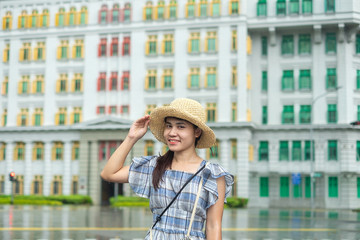 Fototapete - Young Woman traveling with hat, happy Asian traveler visit at rainbow colorful building in Clarke Quay, Singapore. landmark and popular for tourist attractions. Asia Travel concept