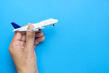 Airplane model in businessman hand on blue background