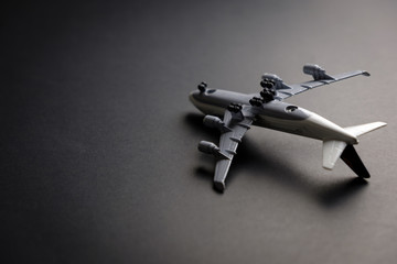 Commercial airplane model upside down on dark background for concept of aerial disaster.