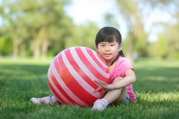 Little Asian baby girl pose with a red white color ball in park during summer or spring