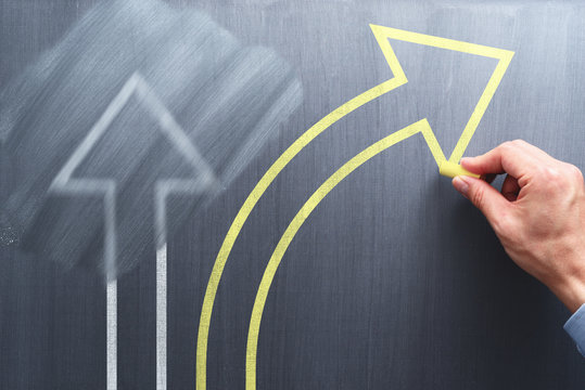 Changing business management concept. Businessman erasing white arrow and drawing yellow arrow on chalkboard.