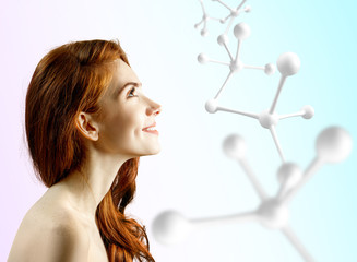 Beautiful redhead woman near big white molecule structure.