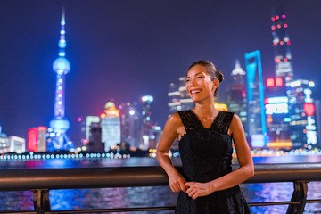 Elegant Asian woman smiling enjoying night club going out in black fashion dress by the Bund river in Shanghai view of city lights of Pudong skyline. Luxury travel lifestyle.