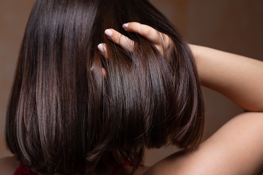 A sexy young Caucasian girl is seen from behind using her fingers to play with her long brown hair. Pulling it up to create a bob style on the back of her head.