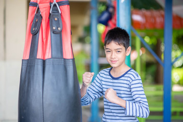 Little Asian boy learn and train boxing with punch bag