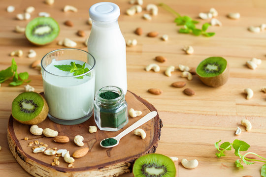 Organic summer breakfast with superfood spirulina, yogurt, kiwi, mint and nuts on wooden table. Meal that promotes good digestion and functioning of gastrointestinal tract. Healthy food concept.