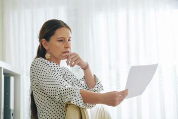 Portrait of pensive female entrepreneur reading document with good offer from investor