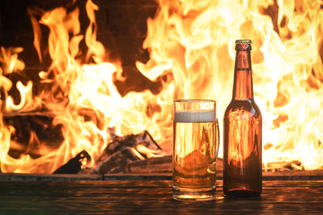 Beer in a mug and a bottle of alcohol on a wooden table on a burning fire in a fireplace background.