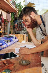Serious bearded carpenter talking on phone with client and drawing sketch of furniture iteam on paper sheet