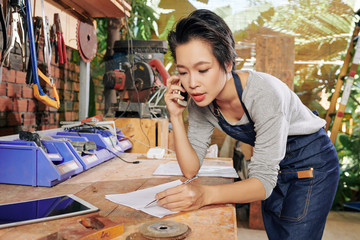 Young female carpenter talking on phone and writing down details of order