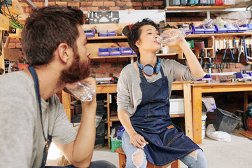 Pretty Asian female carpenter in denim apron drinking bottle of fresh pure water