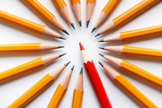 Group of classic yellow pencils surrounding red leader