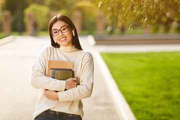 Happy girl with books listening music in campus