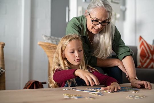 Girl doing jigsaw puzzle with grandmother