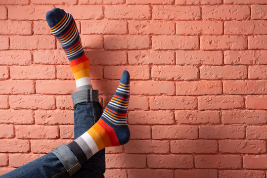 two male legs in colored socks leaning on a brick wall, concept