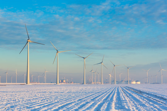 Windmills in a white winter landscape with snow producing green and sustainable energy to reduce global warming - Eemshaven, Groningen, The Netherlands