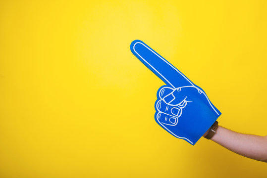 Photo of a handsome arm,  wearing a big blue fan glove, over isolated yellow background