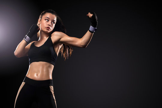 Sportsman, woman boxer fighting in gloves on black background. Boxing and fitness concept.