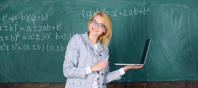 Learn it easy way. Woman teacher wear eyeglasses holds laptop surfing internet. Educator smart clever lady with modern laptop surfing internet chalkboard background. Digital technologies concept