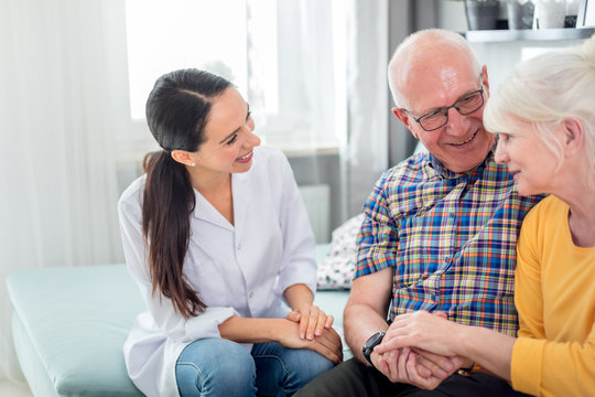 Smiling nurse talking with senior couple during home visit
