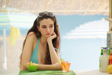 Sad lonely woman having a drink at the beach