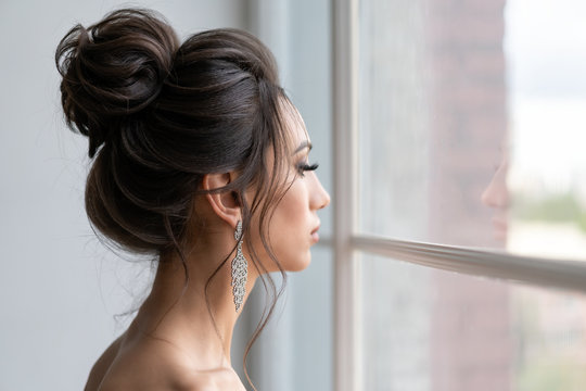 beautiful girl with hairstyle high beam looks out window. Evening image girl.