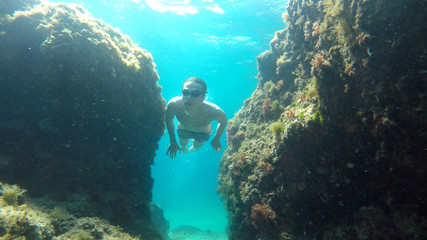young man dives between rocks in the sea