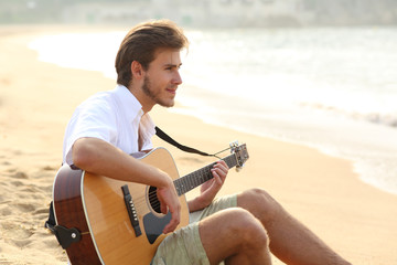 Man playing guitar sitting on the beach