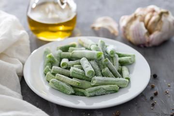 frozen green beans on white plate on ceramic background
