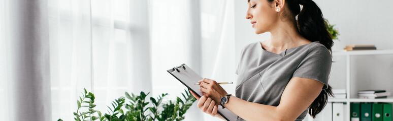 panoramic shot of pregnant woman taking notes in notebook in office