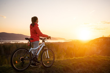 young woman with mountain bike at the sunset.