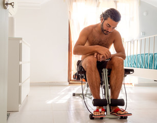 Brunet man on household gym chair during workout in bedroom