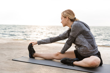 Image of caucasian focused woman doing exercise on mat while working out on pier near seaside in morning