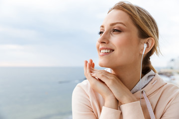 Image of nice woman smiling and listening to music with earphones while sitting near seaside in morning