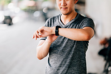 Male in gray T-shirt checking fitness tracker while standing on blurred background of city street during outdoor workout