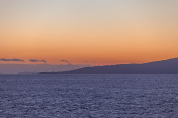 Partially cloudy sky at sunset over the islands of the Saronic Gulf