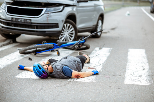 Scene of a road accident with injured cyclist lying on the pedestrian crossing near the broken bicycle and car