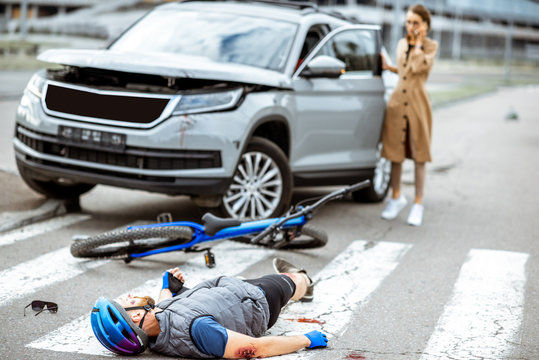 Road accident with injured cyclist lying on the pedestrian crossing near the broken bicycle and worried woman driver and car on the background