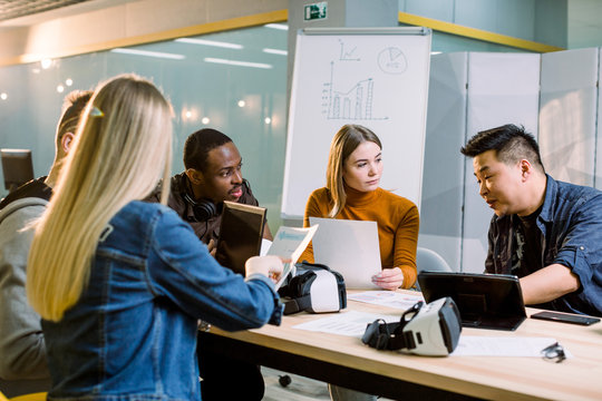 Male and Female Architects or freelancers Work with tablets and laptops, virtual Reality Headsets. High Tech Office Professional People Use Virtual Reality Modeling Software Application.