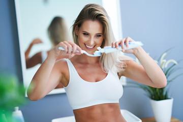 Beautiful woman brushing teeth in the bathroom