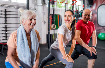 Personal trainer with senior couple doing rehab exercises at the gym Fototapete