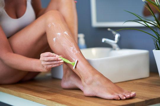 Beautiful woman shaving legs in the bathroom