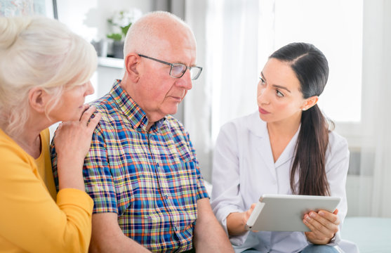 Nurse gives bad news to worried senior couple at home
