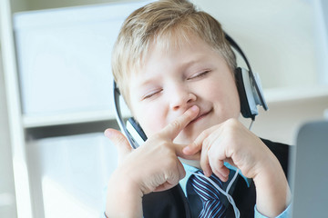 Cute happy 6 year old boy in suit listening to music or audio tutorial on headphones at the office background.