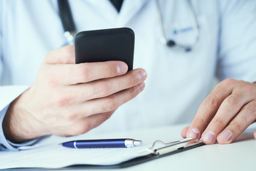 Male doctor hands with mobile phone close-up. Medicine doctor in white coat is using a modern smartphone device with touch screen.