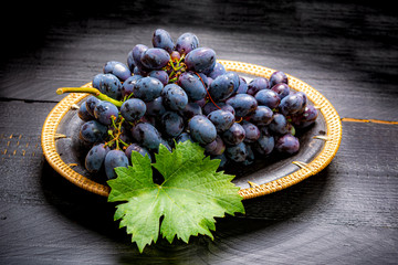 Bunch of ripe blue-black table grape with leaf served on black plate on black wooden background Fototapete