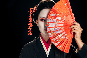 attractive geisha in black kimono with flowers in hair holding bright hand fan isolated on black