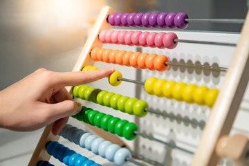 Male hand calculating with beads on wooden rainbow abacus for number calculation. Mathematics learning concept Fototapete